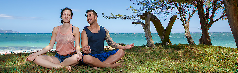 Woman and man meditating or doing yoga on a beach in Maui